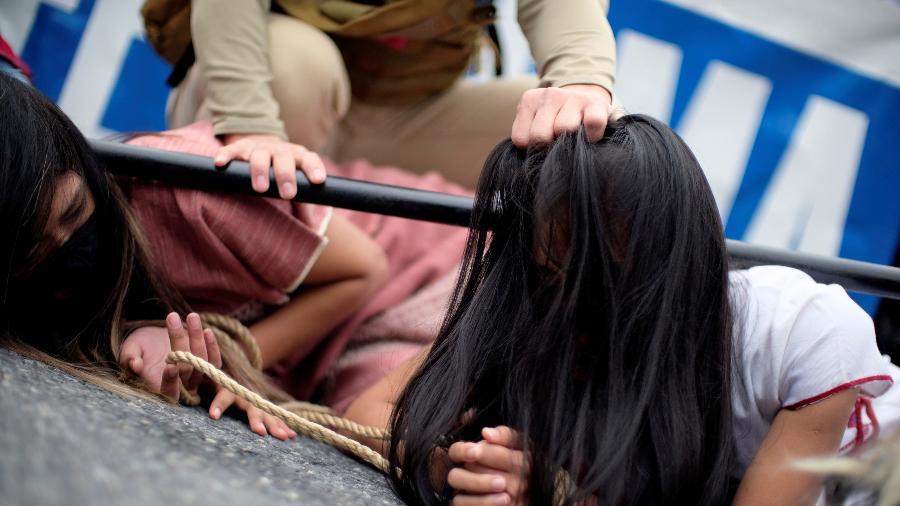 Ativistas fizeram uma demonstração simulada de violência e abuso durante um protesto contra o golpe militar em Mianmar, em frente à embaixada da China em Washington, EUA - JAMES LAWLER DUGGAN/REUTERS