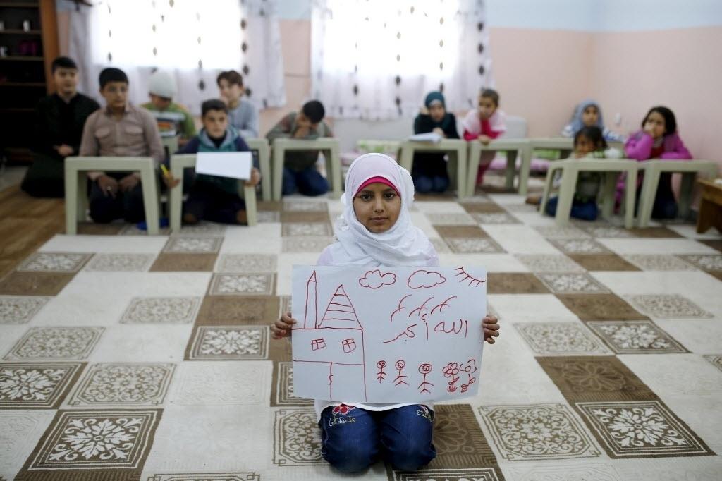 A refugiada síria Islem Halife, 11, mostra um desenho de sua casa na Síria, de dentro da sala de aula onde aprende o Alcorão no campo de refugiados de Nizip, na província de Gaziantep, Turquia. Na escrita em árabe do desenho lê-se