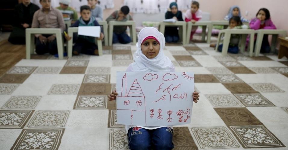 """A refugiada síria Islem Halife, 11, mostra um desenho de sua casa na Síria, de dentro da sala de aula onde aprende o Alcorão no campo de refugiados de Nizip, na província de Gaziantep, Turquia. Na escrita em árabe do desenho lê-se """"Deus é bom"""". A guerra civil na Síria, que já deixou centenas de milhares de mortos, empurra outros tantos para o exílio, entre muitos deles crianças. Os desenhos das crianças do acampamento mostram memórias de suas casas, traumas vividos e esperanças para o seu futuro. Dos 2,3 milhões de refugiados sírios que vivem na Turquia, mais da metade são crianças"""