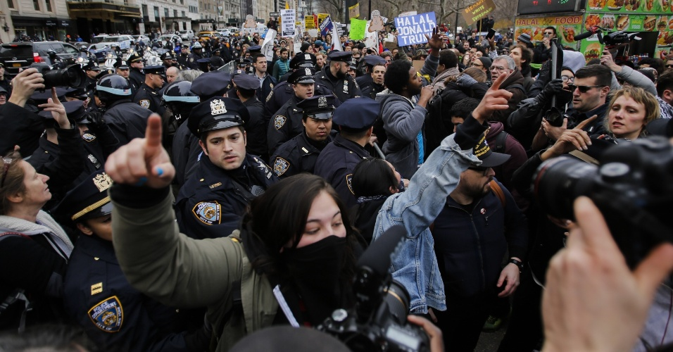 19.mar.2016 - Polícia tenta conter manifestantes contra o pré-candidato republicano Donald Trump em Nova York, nos EUA. O grupo realizou uma marcha contra as propostas do magnata
