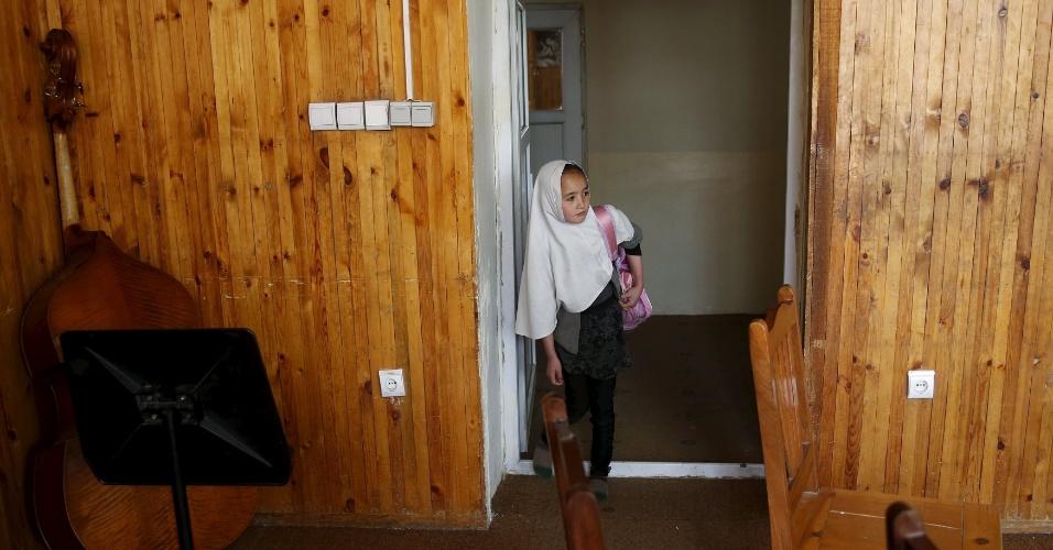 18.abr.2016 - Menina chega a uma das salas do Instituto Nacional de Música do Afeganistão, em Cabul. Tocar instrumento musicais foi uma prática banida durante a vigência do regime do Taleban, no Afeganistão. Ainda hoje, muitos muçulmanos conservadores desaprovam a maioria das formas de música