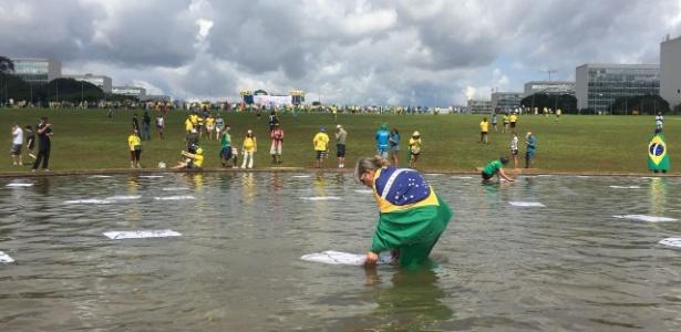 Manifestantes entram em espelho d?água em frente ao Congresso Nacional, em Brasília, e espalham papéis com desenho de ratos, durante um protesto anticorrupção