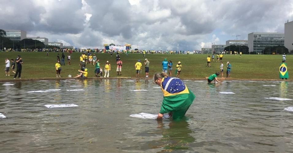 4.dez.2016 - Manifestantes entram em espelho d'água em frente ao Congresso Nacional, em Brasília, e espalham papéis com desenho de ratos, durante um protesto anticorrupção