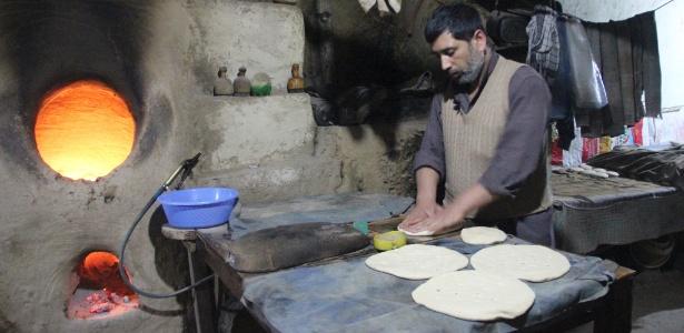 Allah Mohammed faz a massa de pão para vender em Kunduz, no Afeganistão