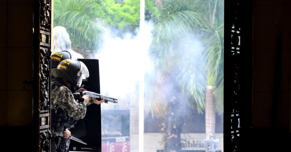 9.fev.2017 - Homens da Força Nacional disparam balas de borracha das portas da Alerj, no Centro do Rio, durante confronto entre manifestantes e policiais militares. Servidores públicos protestam contra o pacote de austeridade do governo Pezão e a privatização da Cedae