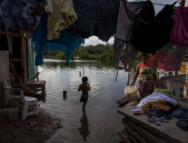 Crianças brincam em área alagada de favela do Recife