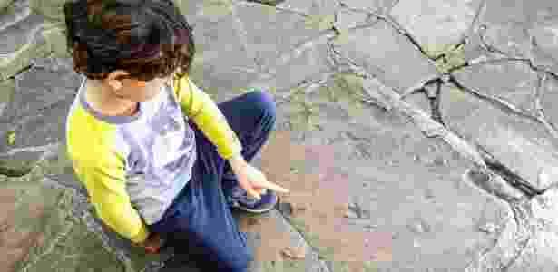6.jul.2017 - Menino mostra marcas nas calçadas que são vestígios de animais pré-históricos de 140 milhões de anos - Gabriela Biló/Estadão Conteúdo - Gabriela Biló/Estadão Conteúdo