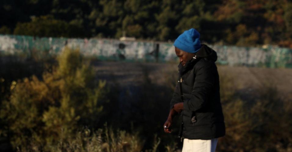 Imigrante reza às margens de um rio antes de tentar cruzar a fronteira para a França