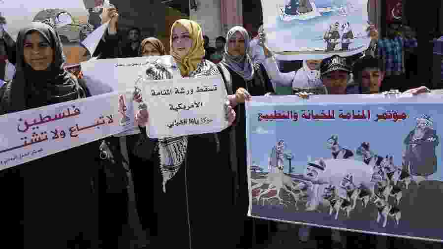 """Manifestantes palestinos gritam slogans por trás de um cartaz com os rostos de líderes árabes sobre corpos de cães e porcos e um slogan em árabe: """"A conferência de traição e normalização em Manama"""" durante um protesto contra uma conferência econômica do Oriente Médio patrocinada pelos EUA no Bahrein - Said Khatib/AFP"""