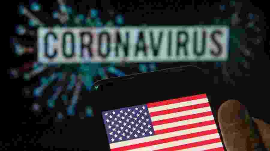 Bandeira dos Estados Unidos (EUA) em frente ao nome do coronavírus - Budrul Chukrut/SOPA Images/LightRocket via Getty Images