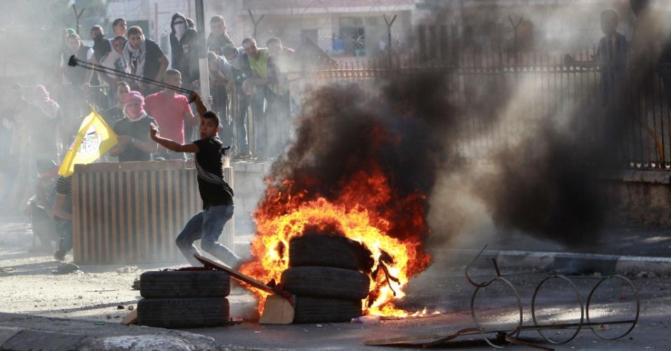 7.out.2015 - Jovem palestinos usa estilingue para atirar pedras em direção as forças de segurança israelenses durante confrontos na entrada principal da Cisjordânia. A ação ocorreu após o funeral do palestino Abdel Rahman Abdullah, 13, morto a tiros pelo exército israelense durante confrontos en um campo de refugiados perto de Belém