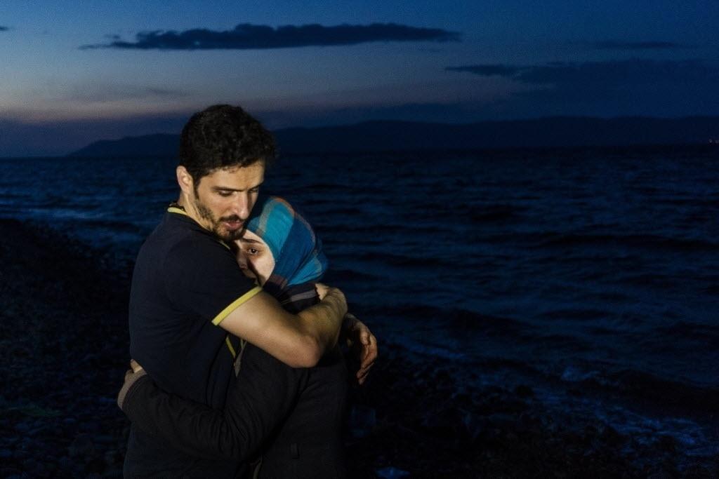 9.out.2015 - Um homem abraça sua mulher ao chegar com outros migrantes em um barco na ilha de Lesbos, na Grécia, após atravessar o mar Egeu saindo da Turquia