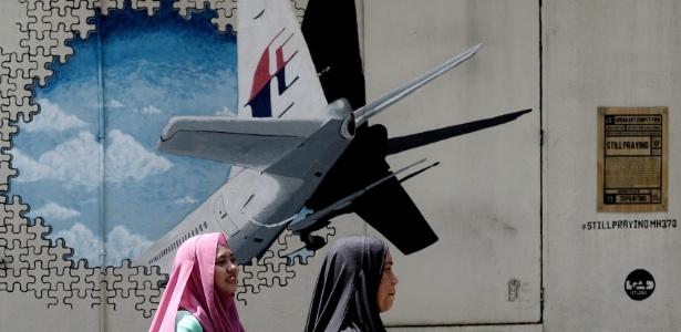 Mulheres passam por mural do voo Mh370 em Shah Alam, na Malásia