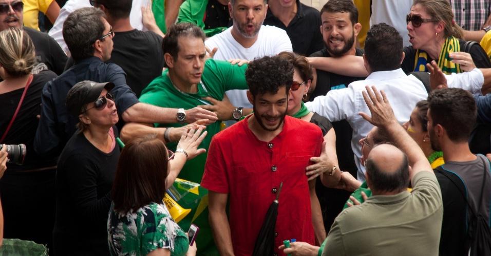 17.mar.2016 - Rapaz vestido com uma camiseta vermelha, cor usada pelo Partido dos Trabalhadores (PT), é hostilizado por manifestantes que protestavam na avenida Paulista, São Paulo, contra o governo de Dilma Rousseff