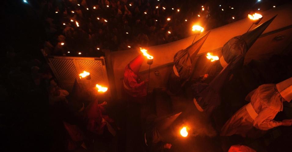 23.mar.2016 - A indumentária brilhante, as máscaras pontiagudas cobrindo o rosto e as tochas são símbolo da procissão do Fogaréu de Goiás