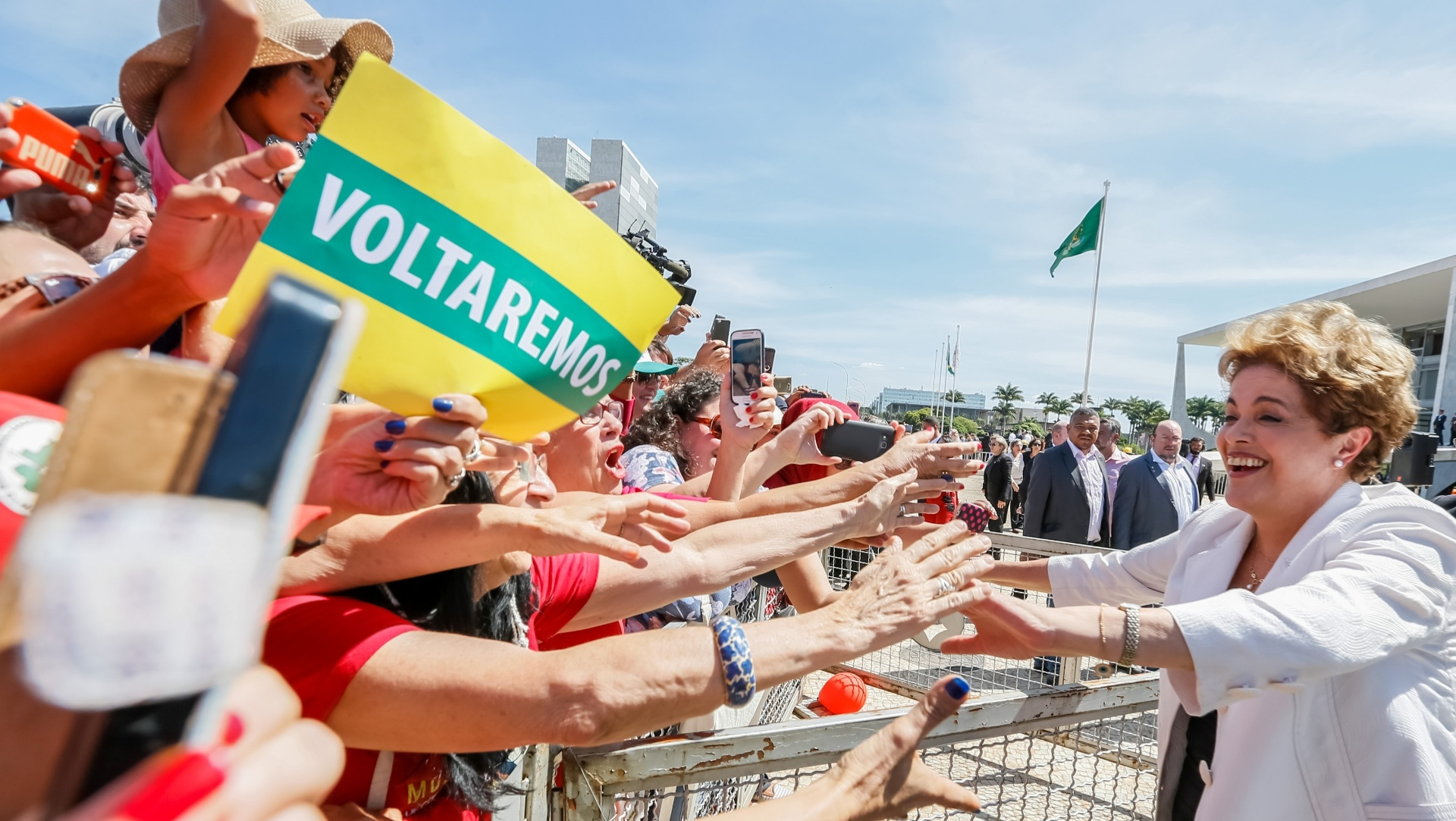 11.mai.2016 - A presidente afastada Dilma Rousseff (PT) é recebida por apoiadores ao deixar o Palácio do Planalto, em Brasília, depois de realizar discurso. Um dos manifestantes contrários ao impeachment exibiu um cartaz com a palavra