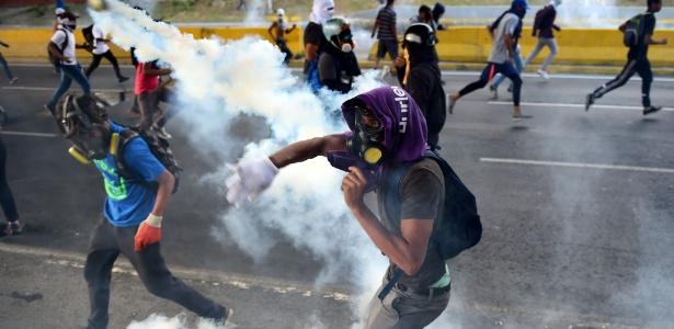 Opositores venezuelanos em confronto com a polícia durante protesto contra o presidente Nicolas Maduro em Caracas