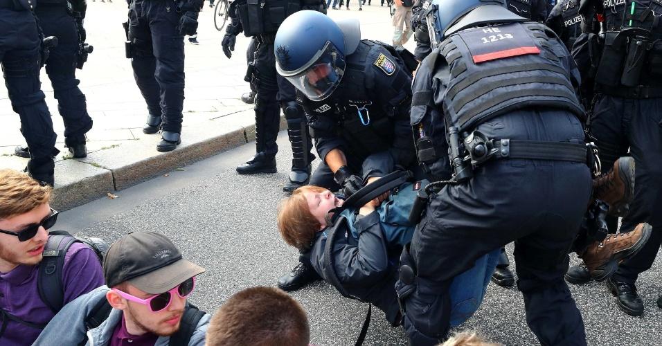 7.JUL.2017 - Polícia alemã detém manifestante que bloqueava rua em manifestação contra a cúpula do G20 na manhã desta sexta-feira
