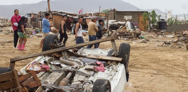 Moradores passam perto de veículo tombado após passagem da tempestade em Los Cabos