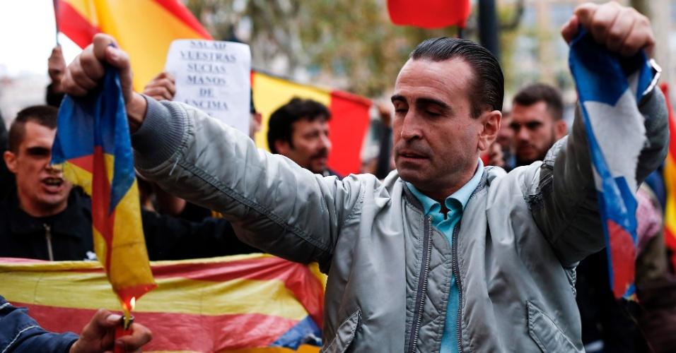 1º.out.2017 - Manifestante segura bandeira da Catalunha rasgada enquanto outro tenta queimá-la durante manifestações convocadas por grupos de extrema direta contra o referendo