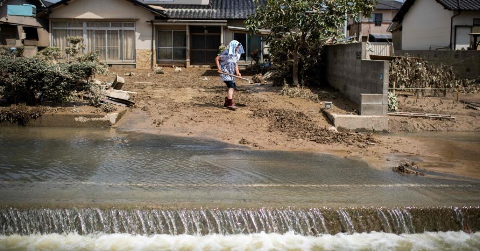 10.jul.2018 - Mulher remove a lama de sua casa danificada em uma área atingida pela inundação