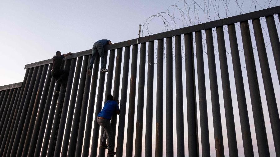 Mexicanos escalam a fronteira México-Estados Unidos em Tijuana - AFP