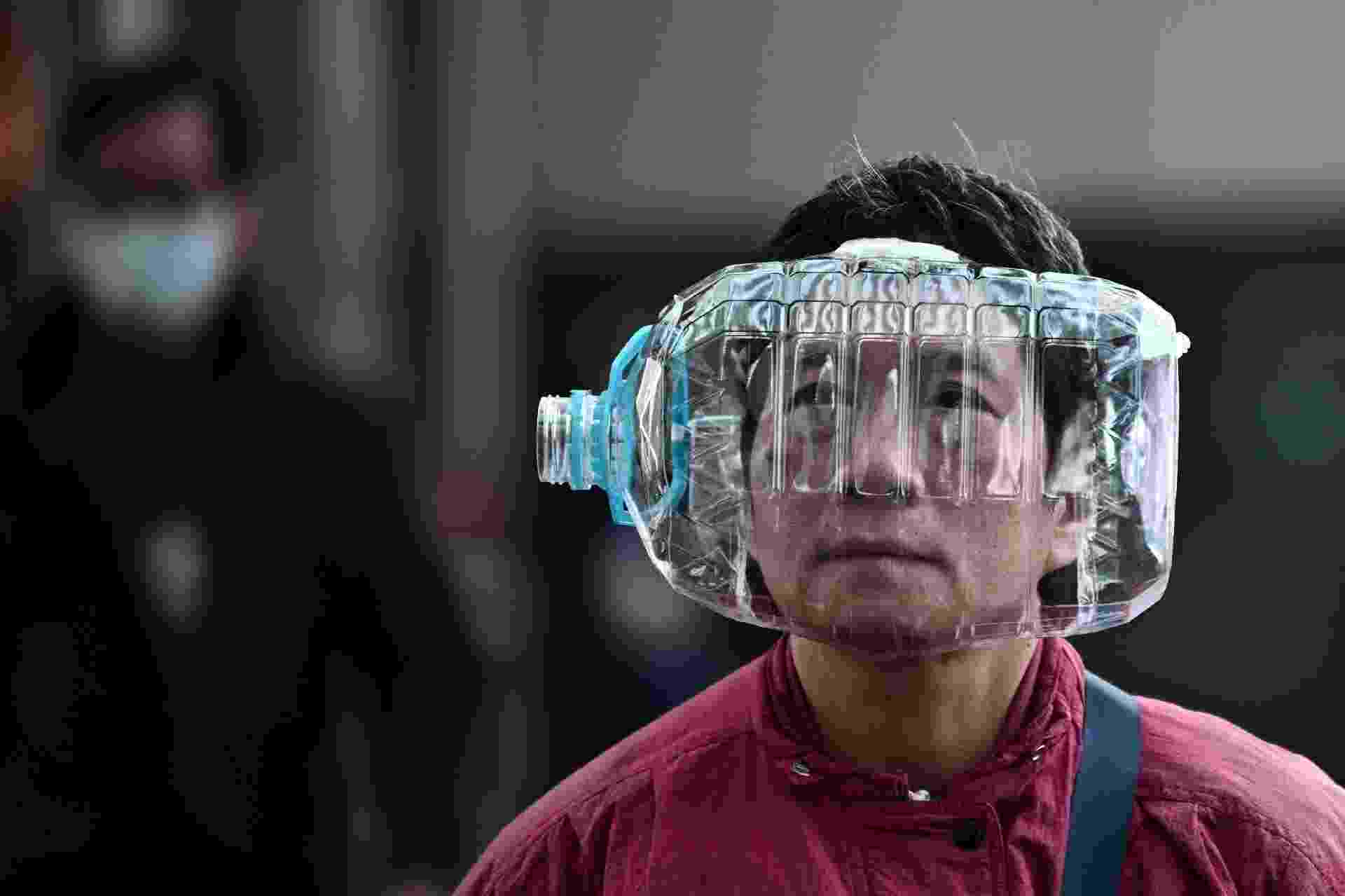 31.jan.2020 - Mulher usa uma garrafa plástica para refirçar a proteção contra o coronavírus, em Hong Kong - ANTHONY WALLACE/AFP