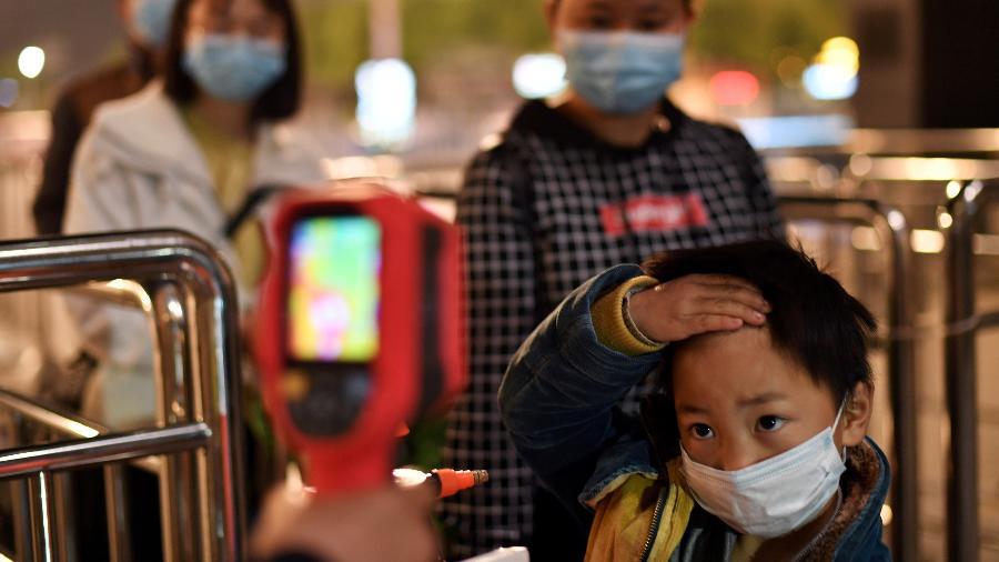 08.abr.2020 - Criança tem temperatura corporal medida do lado de fora da estação de trem de Hankou, na China  - Stringer/Reuters