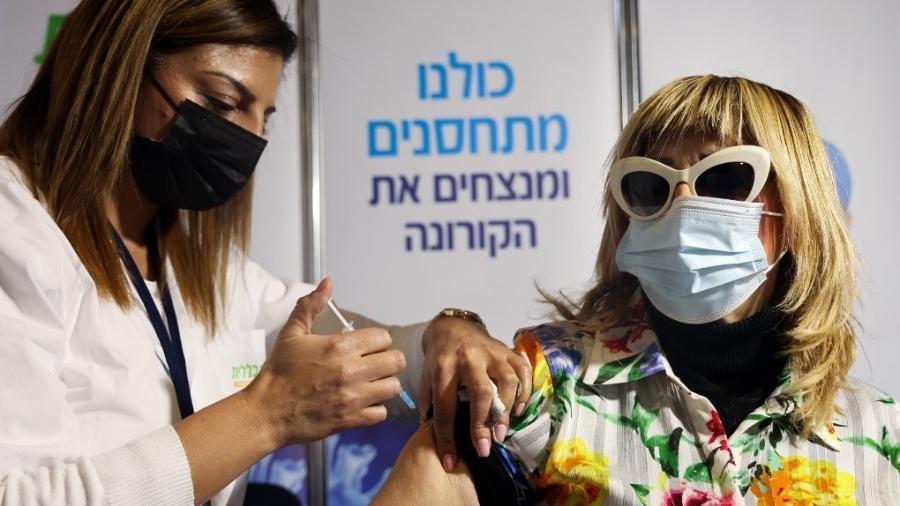 Profissional de saúde vacina mulher em Israel com dose da Pfizer/BioNtech contra a covid-19 em janeiro de 2021 - Emmanuel Dunand/AFP