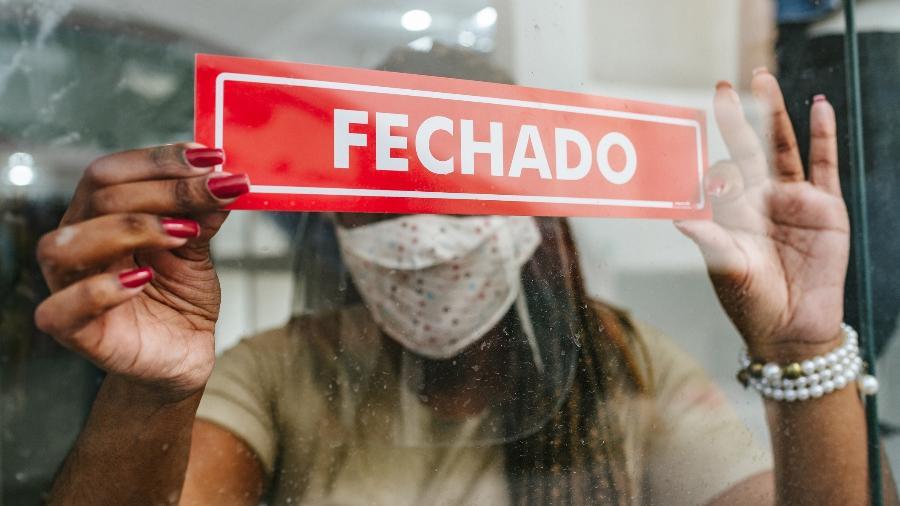 """Mulher segura placa em que se lê """"fechado"""" na porta de um estabelecimento comercial - iStock"""