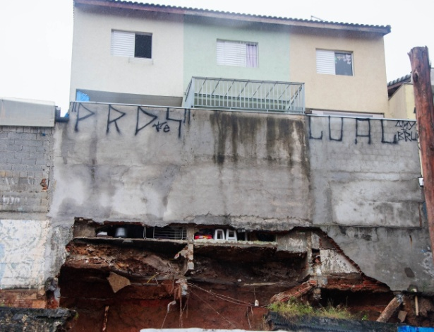 12.jan.2016 - Seis casas foram interditadas pela Defesa Civil por risco de queda na avenida Itaquera, zona leste de São Paulo. Um muro de arrimo cedeu na noite desta segunda-feira (11) após forte chuva que atingiu a cidade