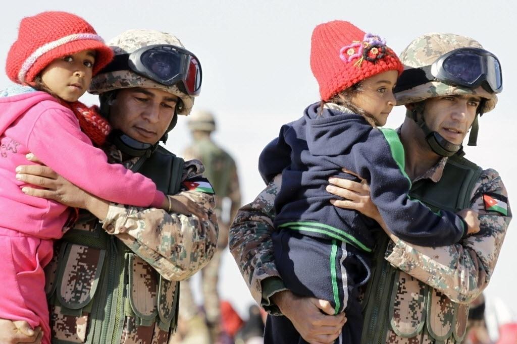 15.jan.2016 - Soldados das forças de segurança da Jordânia ajudam meninas sírias que acabaram de cruzar a fronteira entre os países. O número de refugiados que tentam deixar a Síria e acabam bloqueados nas zonas de fronteira da Jordânia subiu de 12 mil para quase 16 mil desde dezembro de 2015