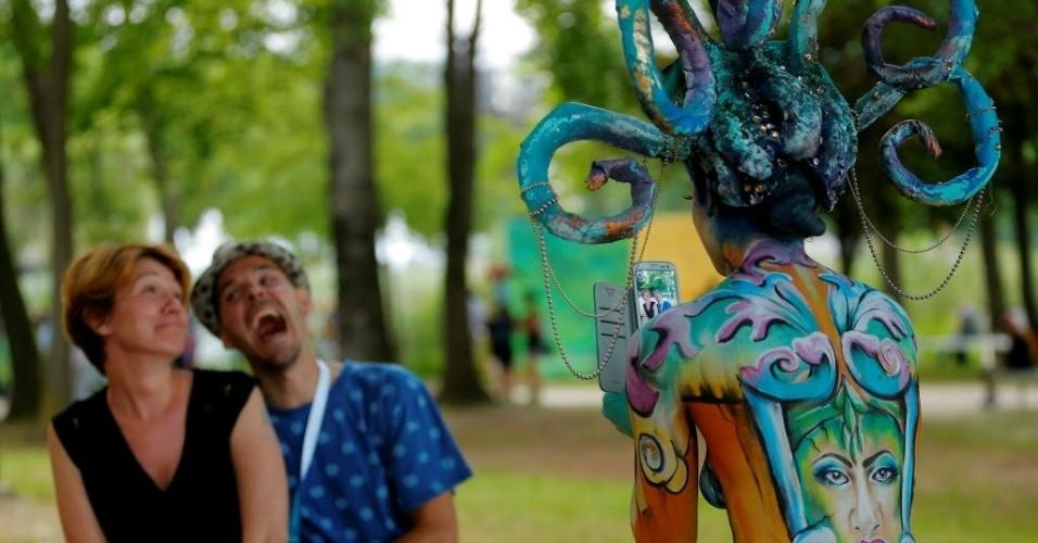 1º.jul.2016 - Modelo com o corpo todo pintado tira foto de um casal durante o Festival Mundial de Bodypainting, em Poertschach, Áustria. Esse é o 19º ano do evento, considerado o maior do mundo no segmento