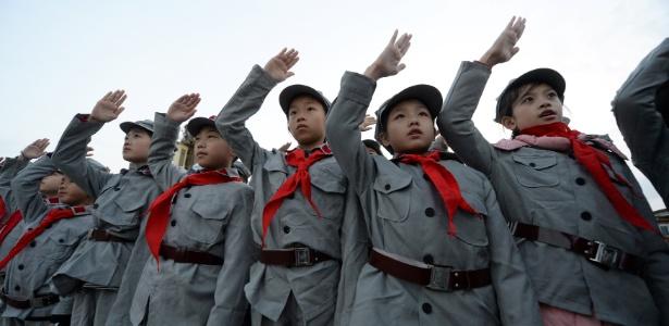 14.out.2017 - Estudantes chineses se vestem com uniformes do Exército Vermelho, durante cerimônia em Pequim