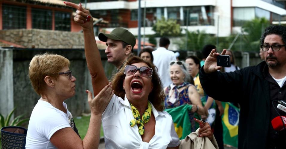 Eleitores do candidato Jair Bolsonaro se manifestam com bandeiras do Brasil e camisetas do presidenciável na porta de seu condomínio na Barra da Tijuca, na zona oeste do Rio de Janeiro