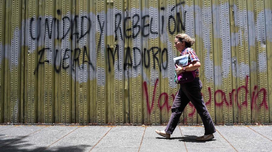 """2.mai.2019 - Mulher passa por muro pichado em que está escrito """"unidade e rebelião, fora, Maduro"""", em Caracas, onde pessoas foram mortas durante os protestos - Federico Parra/AFP"""