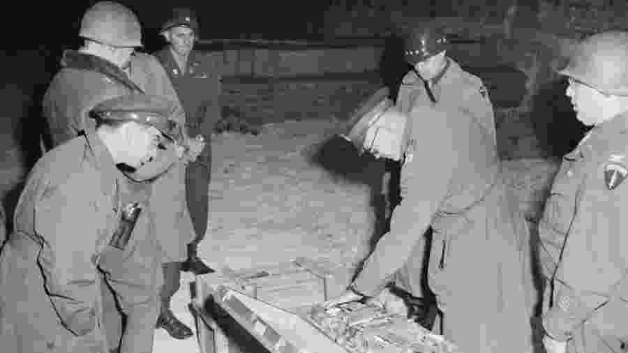 Militares americanos do comando aliado examinam mala de talheres de prata, parte do saque alemão armazenado em uma mina de sal em Merkers - National Archives