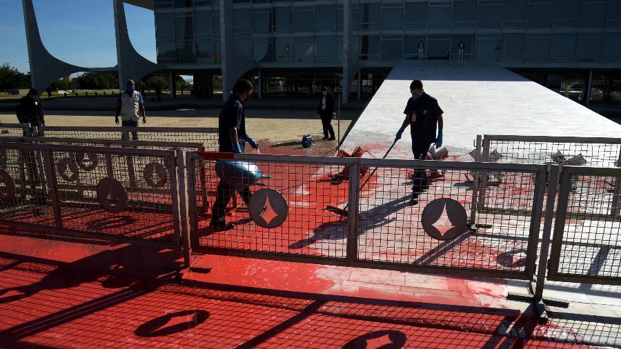 Funcionários limpam a rampa do Palácio após manifestante jogar lata com tinta vermelha - CLÁUDIO REIS/FRAMEPHOTO/FRAMEPHOTO/ESTADÃO CONTEÚDO