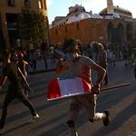 9.ago.2020 - Manifestante carregada bandeira do Líbano enquanto corre junto com outras pessoas após a polícia utilizar gás para afastar protesto em Beirute - Hannah McKay/Reuters