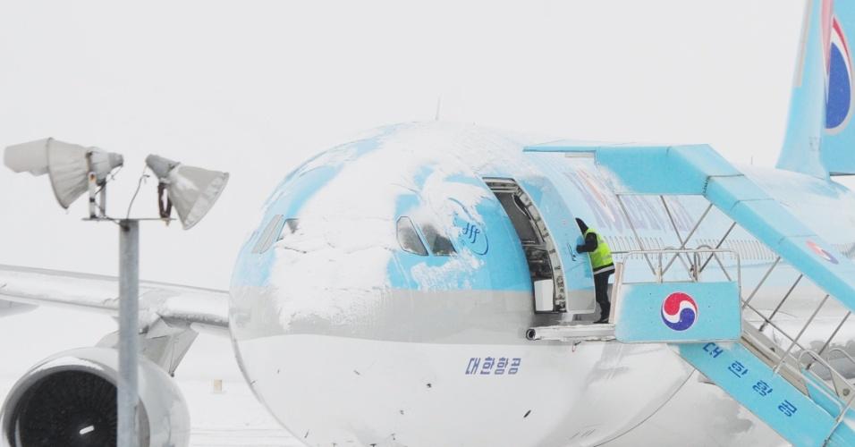 24.jan.2016 - Aeroviário trabalha em avião coberto de neve no aeroporto de Jeju, na Coreia do Sul. Todo o tráfego aéreo do terminal foi interrompido até segunda-feira devido ao mau tempo