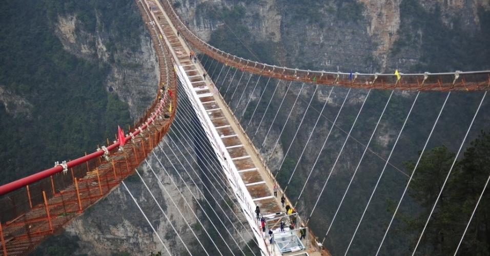 27.jan.2016 - Operários trabalham em ponte de vidro em frente ao Grand Canyon, na província de Hunan, China. A ponte tem 430 metros de comprimento, seis metros de largura e fica a 300 metros acima do vale. Ela é capaz suportar 800 pessoas de uma só vez e deverá ser aberta aos turistas no primeiro semestre deste ano