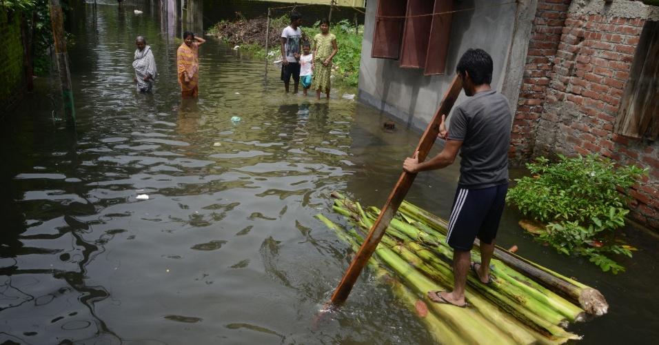 24.jul.2016 - Indiano usa jangada para navegar em área alagada após chuvas contínuas na cidade de Siliguri, que teve estradas afetadas
