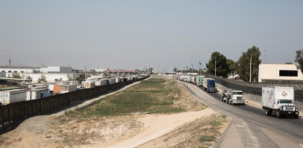 Caminhões entram nos EUA, próximo à fronteira em San Diego, vindos de Tijuana, no México - Eros Hoagland/The New York Times