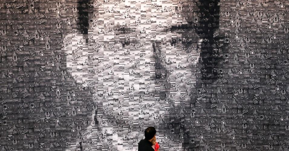 4.nov.2016 - Em Bancoc, capital da Tailândia, homem com criança no colo caminha em frente a painel feito com colagens formando a imagem do último rei do país, Bhumibol Adulyadej, que morreu no dia 13 de outubro após 70 anos no poder