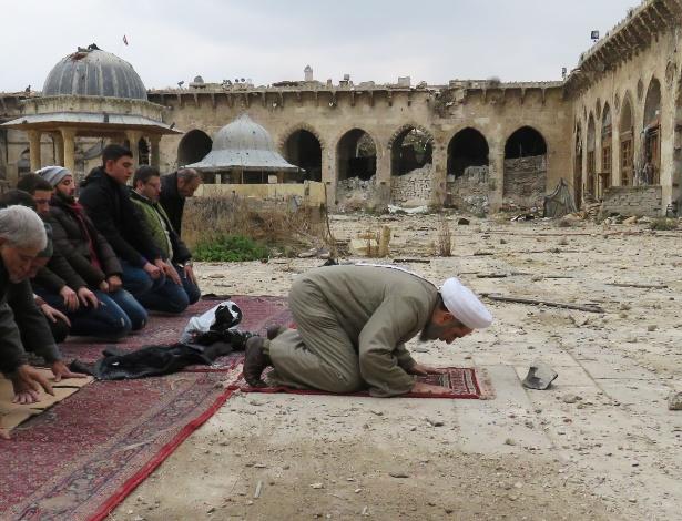 Sírios rezam neste sábado nas ruínas da antiga mesquita de Umayyad, em Aleppo, após civis terem acesso permitido a certas áreas da cidade retomadas pelas forças de segurança do governo