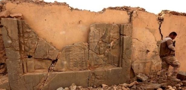 Um soldado caminha em meio a um artefato destruído em Nimrud