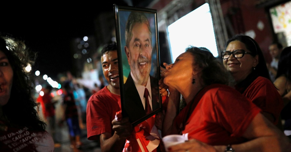 Uma mulher beija foto do ex-presidente Luiz Inácio Lula da Silva, em Fortaleza