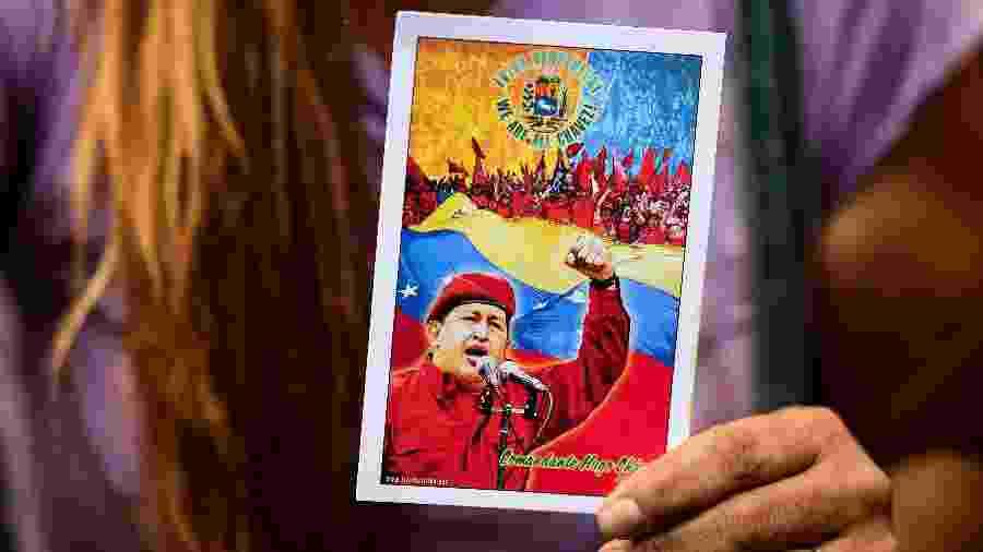 Apoiadora de Nicolás Maduro segura retrato de Hugo Chávez, ex-presidente do país morto em 2013 e uma das maiores lideranças venezuelanas - AFP