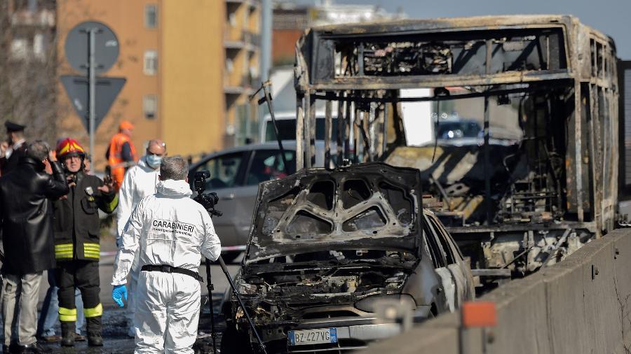 Policiais forenses e membros do corpo de bombeiro trabalham nos restos de um ônibus escolar incendiado nesta quinta (21). O veículo transportava 50 crianças, que se salvaram. Segundo testemunhas o motorista planejava mata-las - AFP