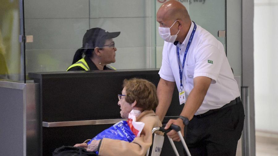 26.fev.2020 - Funcionário do Aeroporto Internacional de Guarulhos, em São Paulo, usa máscara ao auxiliar passageiros. Brasil confirmou primeiro caso do novo coronavírus - NELSON ALMEIDA/AFP